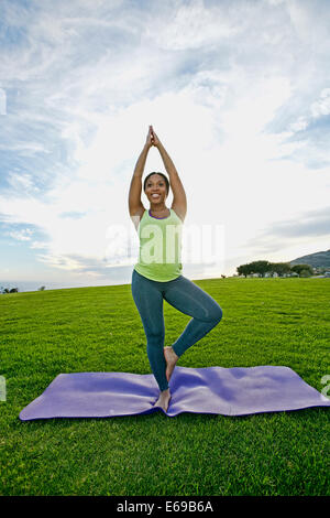 Pregnant woman practicing yoga in park - Stock Photo