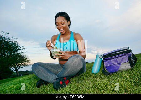 Pregnant woman eating salad in park - Stock Photo