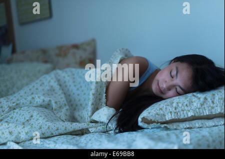 Mixed race teenage girl sleeping in bed - Stock Photo