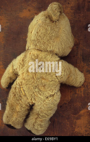 Well worn beige antique teddy bear lying face down on scuffed leather - Stock Photo