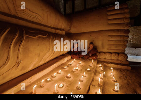 Asian monks lighting candles in temple - Stock Photo