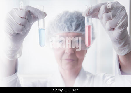 Hispanic scientist examining test tubes in lab - Stock Photo