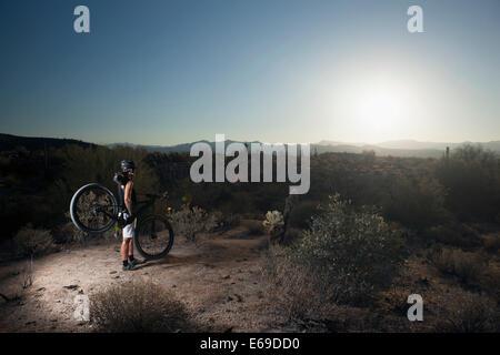 Mountain biker standing in desert