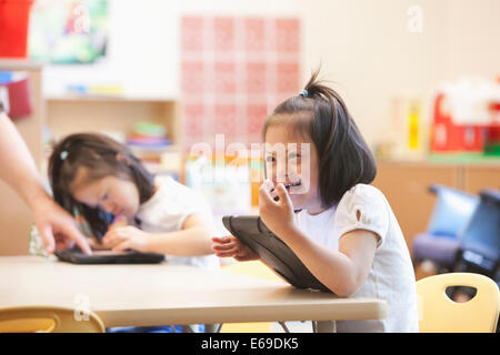 Mixed race Down syndrome student using tablet computer in classroom - Stock Photo