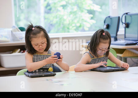 Mixed race Down syndrome students using tablet computers in classroom - Stock Photo