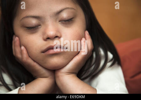 Mixed race Down syndrome girl resting with chin in hands - Stock Photo