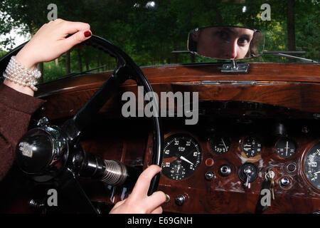 young woman,oldtimer,steering wheel - Stock Photo