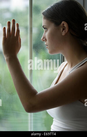 young woman,window,hand,ajar - Stock Photo
