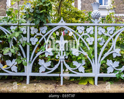 Decorative wrought iron metalwork fence with floral design around garden of house - Richmond upon Thames, Surrey, - Stock Photo
