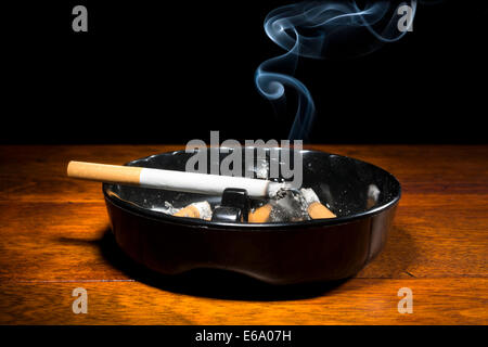 A burning cigar in a classic black ashtray streaming smoking in a dark, moody setting. - Stock Photo