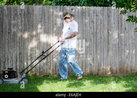 A senior man wearing a hat mows his lawn in dappled sun and shade in Oklahoma, USA - Stock Photo