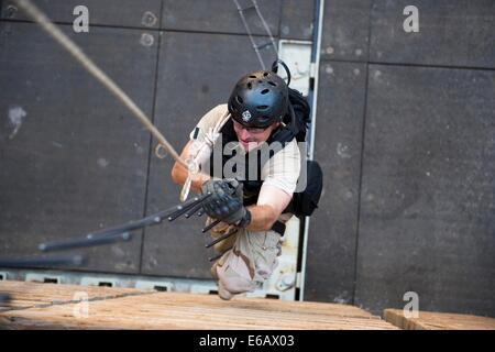 U.S. Navy Boatswain's Mate 3rd Class Chase Burton climbs a caving ladder out of the well deck of the amphibious - Stock Photo