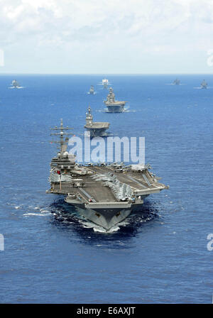 The aircraft carrier USS Ronald Reagan (CVN 76) leads a formation of vessels from 15 international partnership nations - Stock Photo