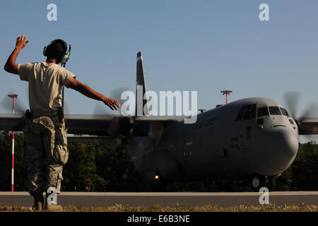 U.S. Air Force Senior Airman Christopher Guerrero, with the 86th Aircraft Maintenance Squadron, marshals a C-130J - Stock Photo