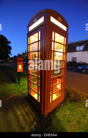 A traditional red telephone box at night in an English village, with a post box in the background. - Stock Photo
