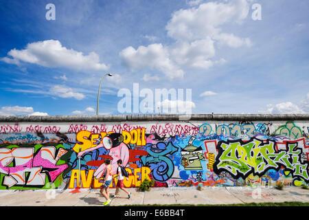 Berlin wall view; Graffiti on original section of Berlin Wall at East Side Gallery in Friedrichshain in Berlin Germany - Stock Photo