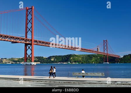 Portugal, Lisbon: People passing near riverside at bridge Ponte 25 de Abril - Stock Photo