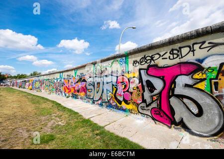 Graffiti on original section of Berlin Wall at East Side Gallery in Friedrichshain in Berlin Germany - Stock Photo
