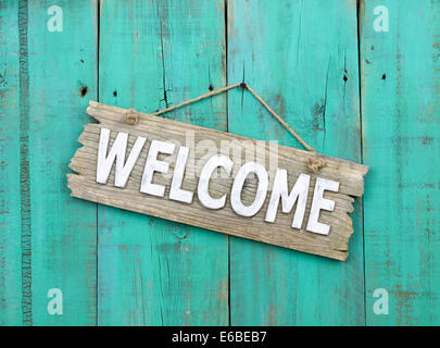 Weathered welcome sign hanging on antique green wood door - Stock Photo