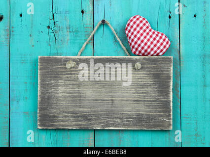Blank distressed sign with red checkered heart hanging on rustic antique teal blue wood door - Stock Photo