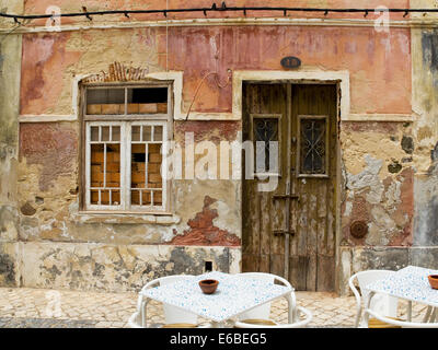Antique wooden door in a house with worn stone wall texture. - Stock Photo