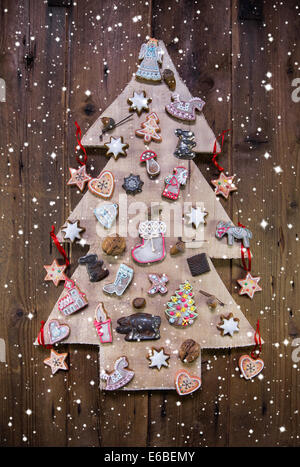 Handmade carved christmas tree decorated with gingerbread, stars and hearts on wooden background. - Stock Photo