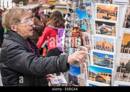 An older woman tourist looks at postcards at a shop along one of the main pedestrian thoroughfares in Venice. - Stock Photo
