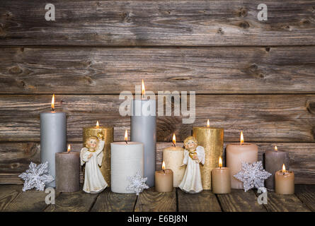 Christmas decoration with candles and golden angels on wooden background. - Stock Photo