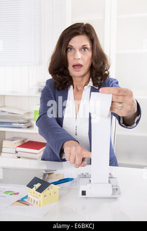 Shocked and frustrated business woman controlling expenses of the company. - Stock Photo