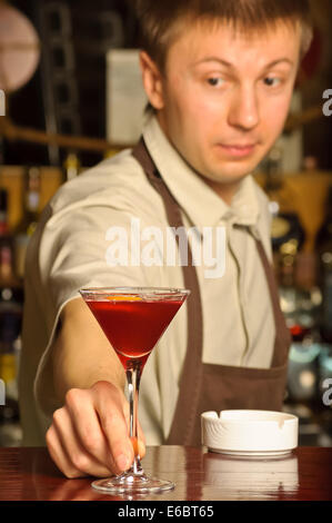 Barman holding the glass with cocktail - indoors - Stock Photo