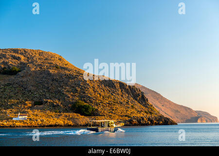 Fishing boat heading out to the mediterranean sea in the early morning - Stock Photo