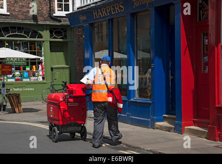 Postman pushing trolley delivering post letters mail in the city town centre York North Yorkshire England UK United - Stock Photo