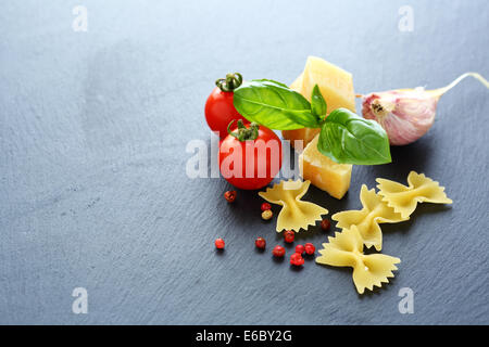 pasta, cheese and tomatoes on slate background, food closeup - Stock Photo