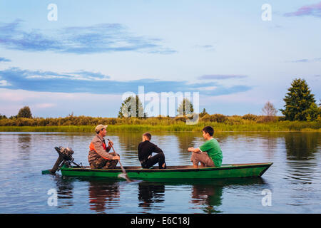 MINSK, BELARUS - JULY 25: Belarusian Man And Two Boys Sailing In Old Boat On River At Sunset Of Summer Day On July - Stock Photo
