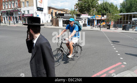 Cyclist man on bike and Orthodox Jewish pedestrian crossing the road in Stamford Hill London N16 UK    KATHY DEWITT - Stock Photo