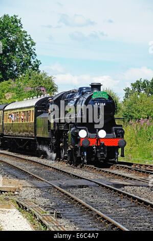 Steam Locomotive Ivatt Class 4 2-6-0 number 43106 in British Rail Black approaching the railway station, Severn - Stock Photo