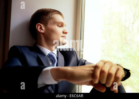 Young man sitting on windowsill - waiting bride - Stock Photo