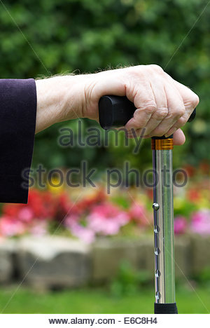 Closeup of senior womans hand holding walking stick - Stock Photo