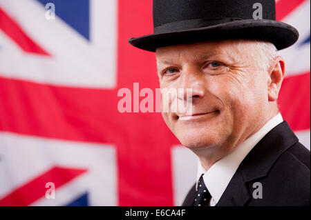 Businessman wearing traditional British bowler hat, and standing in front of the Union Jack national flag of the - Stock Photo
