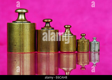 Five old-fashioned antique copper weights in a row - Stock Photo
