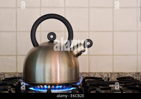 Teapot kettle on gas stove burner - Stock Photo