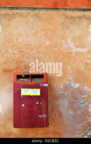 Red Italian mailbox on terracotta / ochre wall, Venice, Italy - Stock Photo