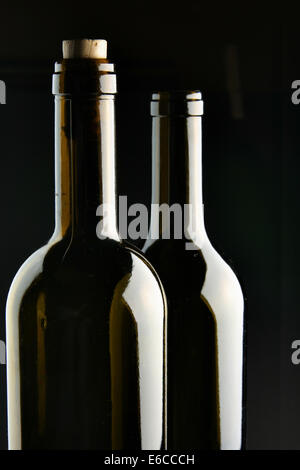 Necks of two bottles over black background - Stock Photo