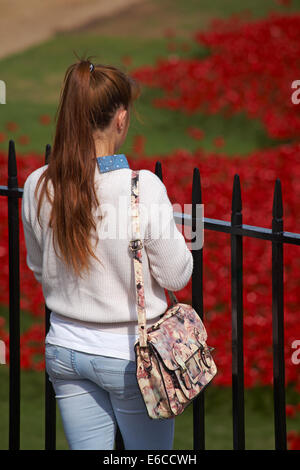 young lady looking at ceramic poppies of Blood Swept Lands and Seas of Red at Tower of London to mark centenary - Stock Photo