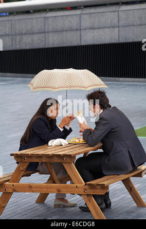 Young couple sitting on bench eating lunch sheltering under umbrella in the rain at Southbank, London in August - Stock Photo
