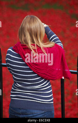 woman photographing the ceramic poppies of Blood Swept Lands and Seas of Red at Tower of London to mark centenary - Stock Photo