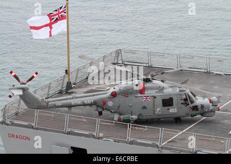 Westland Lynx HMA8 military helicopter on the rear deck of the Royal Navy destroyer HMS Dragon beneath a flying - Stock Photo