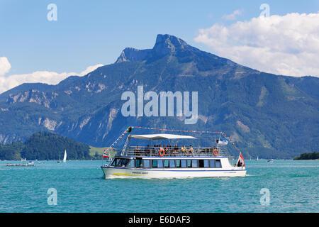 Austria, Upper Austria, Salzkammergut, View of a passenger ship in Mondsee Lake, Schafberg in the background - Stock Photo