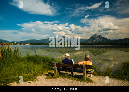 Germany, Bavaria, Allgaeu, East Allgaeu, Lake Hopfensee, near Fuessen, Old couple on wooden bench - Stock Photo