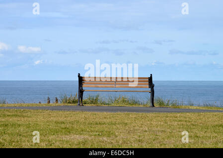Empty wooden bench on seafront in Blackpool, Lancashire, England - Stock Photo